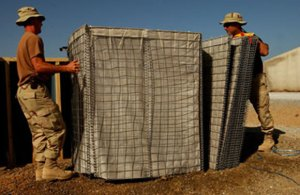 American soldiers unfolding a small HESCO barrier